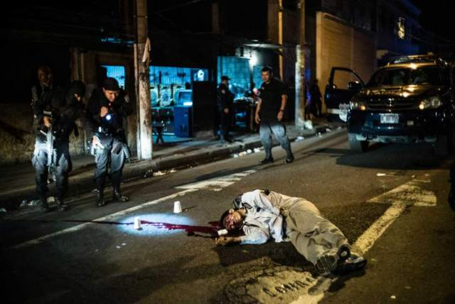 SAN SALVADOR, EL SALVADOR, 2015.05.21: Two policemen study the body of a man murdered at a busy intersection in downtown San Salvador during rush hour. They are part of the 911 response team patrols the streets of the capital. The 'halcones' respond first to crimes involving armed people, homicides and other serious crimes. The first 5 months of 2015 has witnessed a rapid increased in the number of police deaths at the hands of pandillas or gangs.